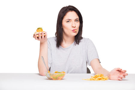 heaving: healthy versus junk food concept with a natural woman heaving in front fruits meal and choosing fries with hamburger, isolated on white