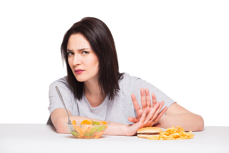 healthy choices: picture of woman with fruits rejecting hamburger