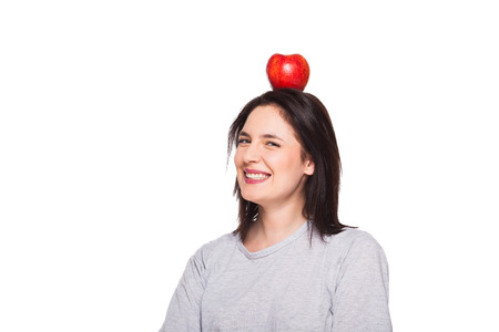 Portrait of a cute brunette with an apple on her head, white background photo
