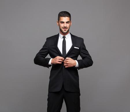 handsome hispanic elegant man in black suit on grey background