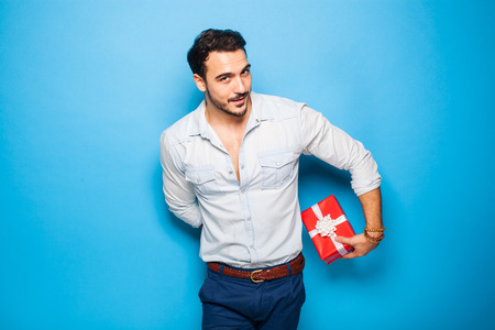 cute guy: cute guy hiding a christmas gift behind him on blue background Stock Photo