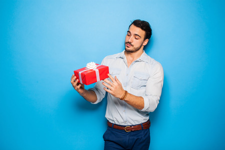 gold gift box: handsome adult man cheking a christmas gift, on blue background