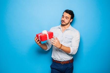 dar un regalo: hombre adulto guapo cheking un regalo de Navidad, sobre fondo azul