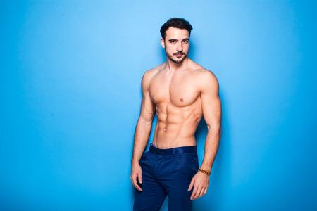ropa interior: hombre sin camisa con barba en el fondo azul