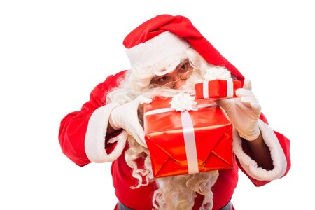 old santa claus with glasses and white gloves holding gifts in his hands, on white background photo