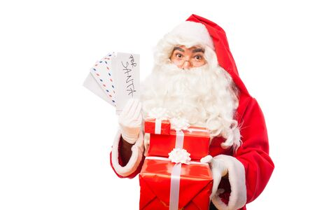 santa claus holding letters from kids and gifts on white background