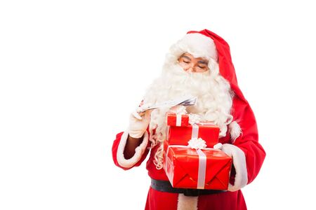 santa claus holding letters from kids and gifts on white background photo