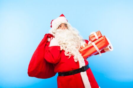 santa clause looking up with sack and gifts in hands