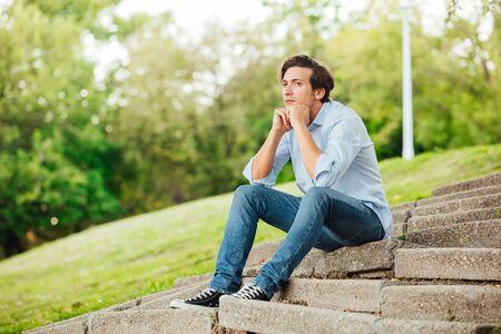 persona pensando: hombre adulto en camisa azul que se sienta sola en las escaleras fuera y pensar