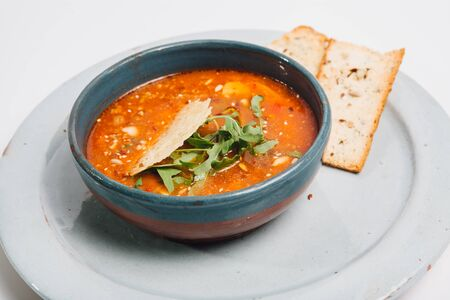 bred: bowl with soup and bred on blue dish