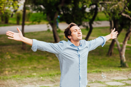 happy adult man celebreting with open arms outside in nature Standard-Bild