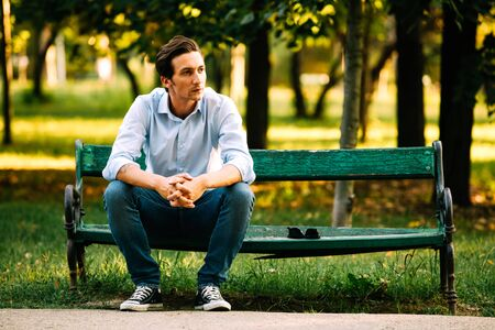 atractive adult man sitting alone on bench in park