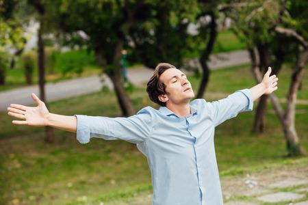 自然の中の外両手を広げて幸せな成人男 celebreting