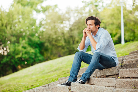 adult man in blue shirt sitting alone on stairs outside and thinking