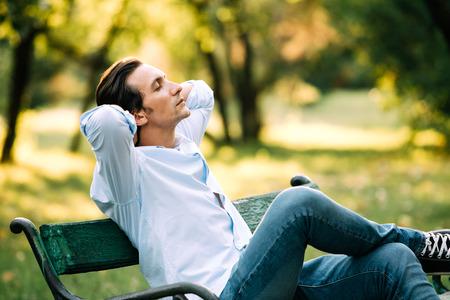 공원 벤치에 혼자 앉아 고 atractive 성인 남자 스톡 콘텐츠