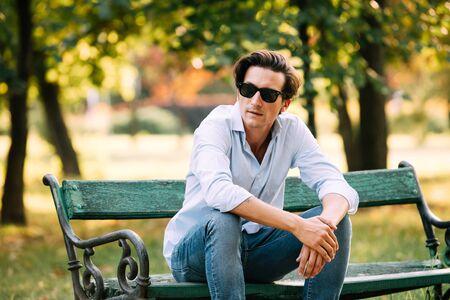 banc de parc: homme séduisant en chemise bleue assis seul sur le banc dans le parc avec téléphone portable et des lunettes de soleil