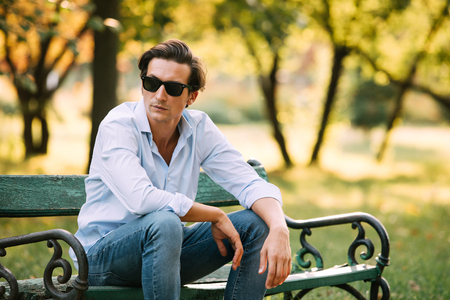 bench alone: attractive man in blue shirt sitting alone on the bench in park with cellphone and sunglasses