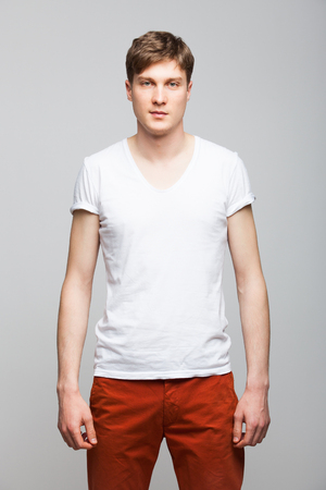 red pants: young man in white tshirt and red pants standing on gray background