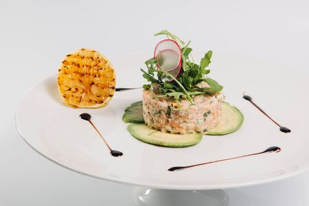 plating: salmon salad with grilled lemon on white plate