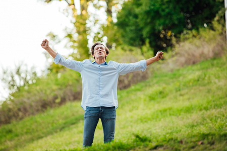 male arm: happy adult man celebreting with open arms outside in nature Stock Photo