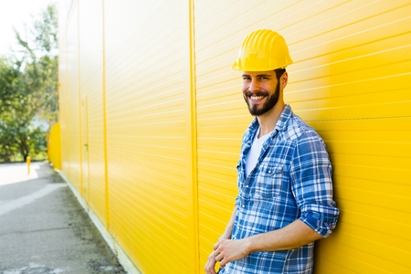 adult wall: worker with helmet and yellow plaid shirt near a wall