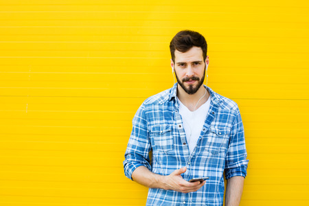 handsfree telephone: young happy man casual dressed with headphones and smart phone on yellow background