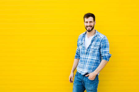handsome young man: handsome man in checkered shirt smiling on yellow background
