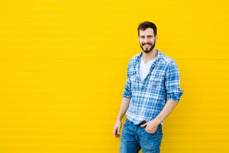 camiseta: hombre guapo en camisa a cuadros sonriente sobre fondo amarillo Foto de archivo