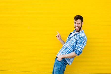 Smiling young man casual dressed standing against yellow background, showing one side