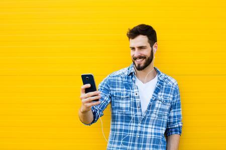 audifonos: casual joven hombre feliz vestida con los auriculares y el teléfono inteligente en fondo amarillo Foto de archivo