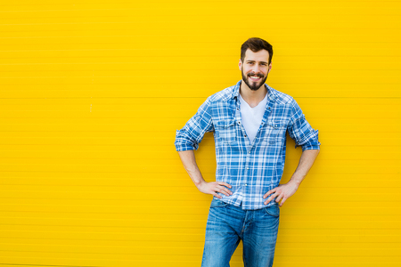 YELLOW: Smiling young man casual dressed standing against yellow background, showing one side