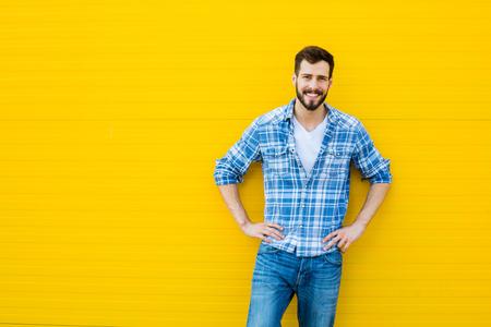 de vaqueros: Sonriente joven vestido casual de pie contra el fondo amarillo, mostrando un lado Foto de archivo