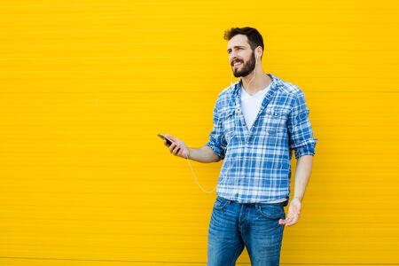 handsfree phones: young man casual dressed with headphones and smart phone on yellow background, concerned