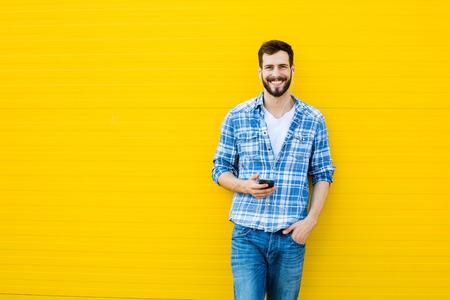 Mladý šťastný muž příležitostná oblečený se sluchátky na uších a chytrý telefon na žlutém pozadí Reklamní fotografie