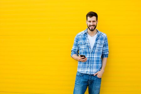 handsfree phone: young happy man casual dressed with headphones and smart phone on yellow background