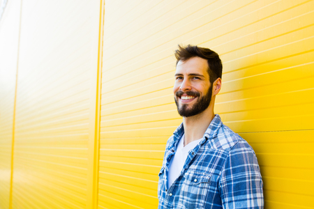 handsome man in checkered shirt smiling on yellow background
