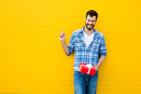 adult man smiling with beard with red present on yellow background, showing on his right text space
