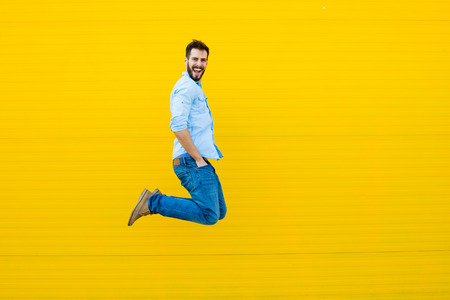 jump: handsome man casual dressed celebrating and jumping on yellow background Stock Photo