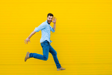 handsome man casual dressed celebrating and jumping on yellow background Banque d'images