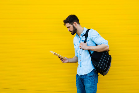 handsome student with bakpack and a book on yellow background 免版税图像