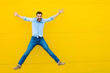 personas saltando: apuesto hombre vestido casual celebrando y saltando sobre fondo amarillo