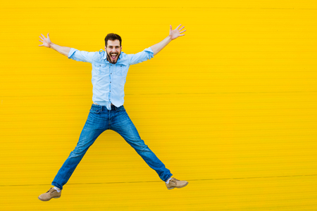 handsome man casual dressed celebrating and jumping on yellow background Stockfoto