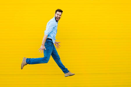 handsome man casual dressed celebrating and jumping on yellow background Stock fotó - 46389298