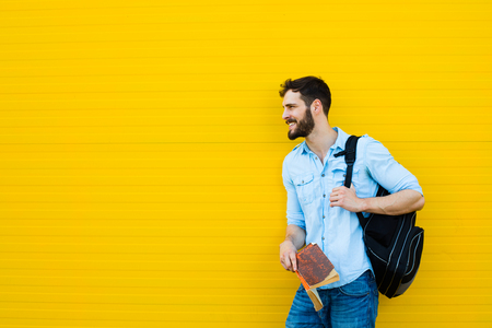 handsome student with bakpack and a book on yellow background Foto de archivo