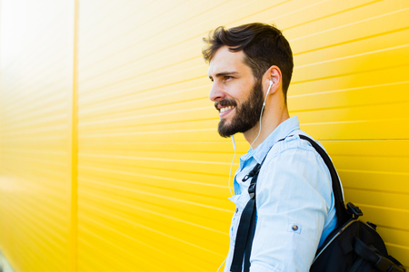 handsome student with bakpack and a book on yellow background Banque d'images