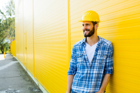 plaid shirt: worker with helmet and yellow plaid shirt near a wall