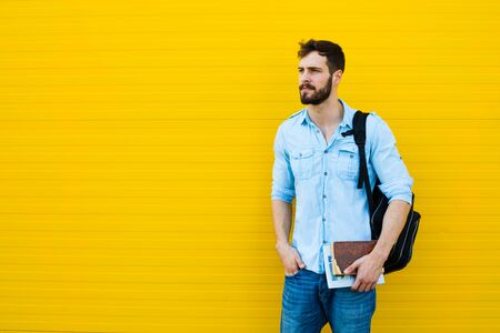 gente adulta: handsome student with bakpack and a book on yellow background Foto de archivo