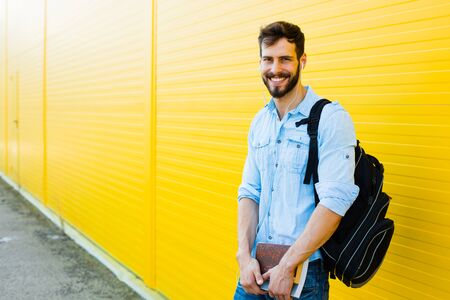 handsome student with bakpack and a book on yellow background Standard-Bild
