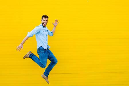 잘 생긴 남자 캐주얼 축하과 노란색 배경에 점프 옷을 입고 스톡 콘텐츠