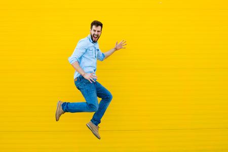 pohledný muž ležérní oblečení slaví a skákání na žlutém pozadí